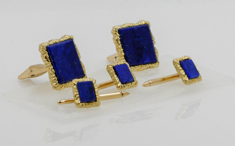 This polished look gives his business attire a classic finish. Made in 14K textured yellow gold, each of these refined men's rectangular cuff links and shirt studs feature a rich  Lapis Lazuli gemstones in a square frame. Buffed to a bright luster,