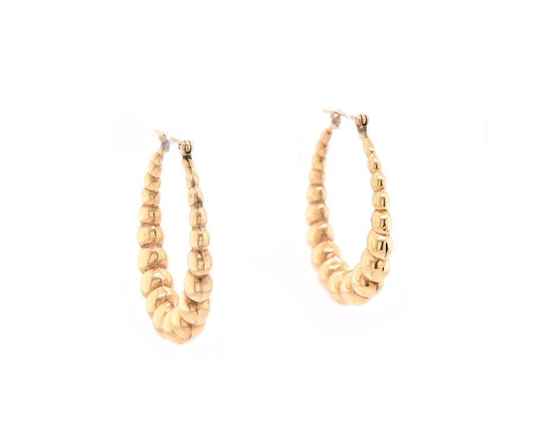 Material: 14k yellow gold Dimensions: earrings measure 37.46mm wide Fastenings: snap closure Weight: 6.40 grams