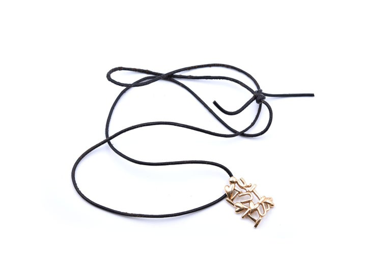 """This pendant is crafted in 14k yellow gold and hangs from a black cord. The pendant depicts the text, """"I Love U.""""  It measures 33x23mm and weighs 17.20 grams. The black cord that the pendant hangs from measures approximately 32- inches in length and"""