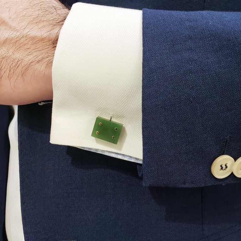 A unique  pair of domino-designed cufflinks showcasing square jades, each finished with four gold buttons. Set in 14k yellow gold with whale backs.