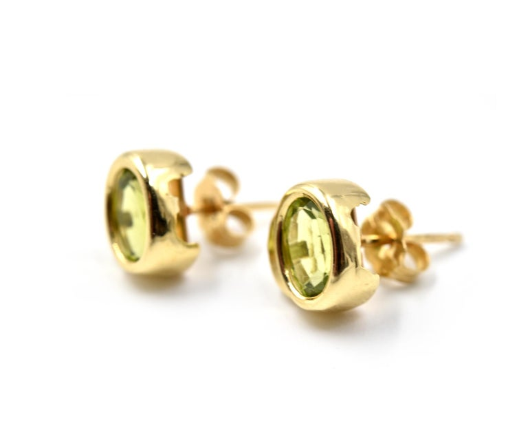 Designer: custom design Material: 14k yellow gold Gemstones: 2 oval peridots' Dimensions: earrings measure approximately 8.45mm by 8.03mm Fastenings: post with friction backs Weight: 2.03 grams