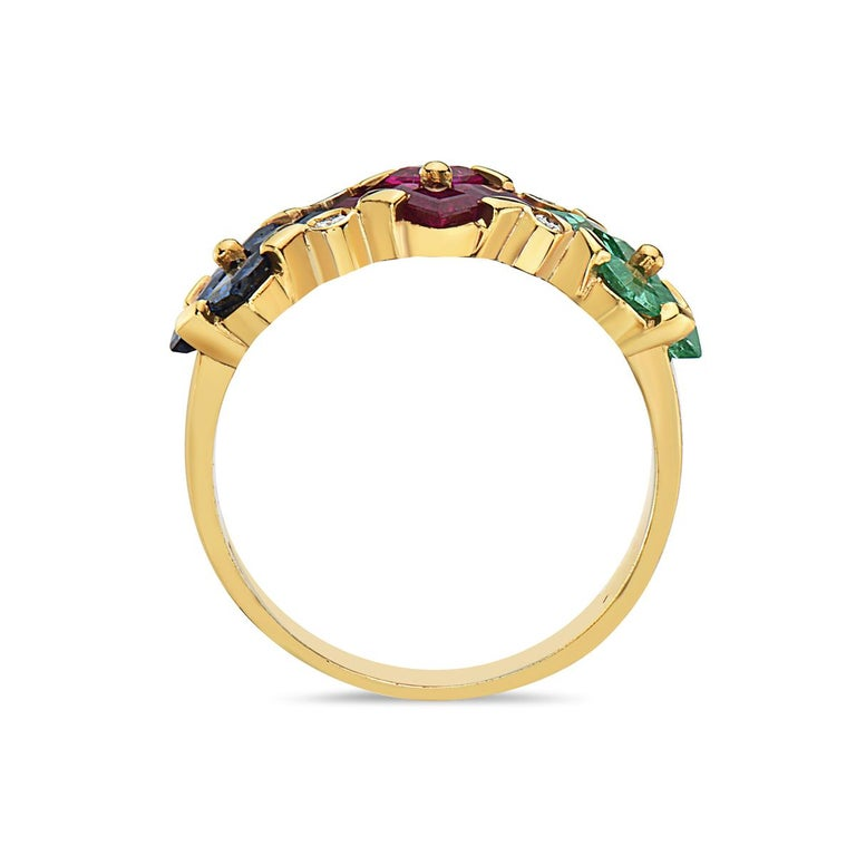 This ring features a mix of ruby, sapphire, emerald, and diamonds set in 14K yellow gold. 4.6 grams total weight. Size 7 3/4.  Viewings available in our NYC showroom by appointment.