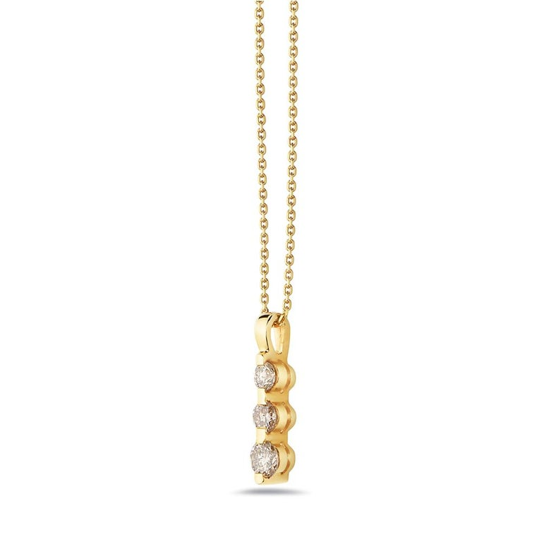 This necklace features three round brilliant diamonds set in 14K yellow gold. Made in USA.    Viewings available in our NYC showroom by appointment.
