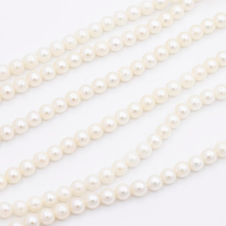 Vintage Three Layer Freshwater Pearl Necklace with a 14kt Yellow Gold Diamond Clasp. There are 97 pearls on one layer, 101 pearls in the middle strand, and 106 pearls in the longest layer. The necklace measures 18