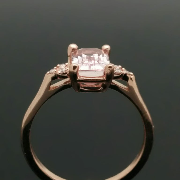 A 14kt rose gold ring set with a spectacular pink, emerald-cut sapphire estimated at 1.92ct. Each shoulder features 3 diamonds with an 0.02 cttw. Estimated weight of gold is 2 gr.   We will size it for you.