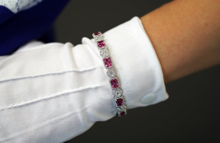 14kt white gold bangle with natural pink sapphires and diamonds. Hallmarked 14kt. Circa 2010+  Dimensions -  Weight : 21 grams Size : 6.6 x 5.9 x 0.8 cm  Pink Sapphire -  Cut : Emerald Number of Pink Sapphires : 7 Each Size : Approx 0.75 ct Total