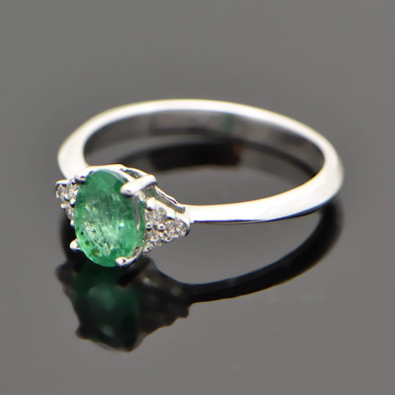 This ring is 14kt white gold featuring an oval cut emerald estimated at 0.72ct and 3 diamonds on each side with an estimated 0.08cttw with a knife's edge band. Estimated weight of gold is 2 gr.   We will size it for you.