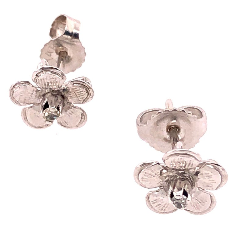 14Kt White Gold Flower Stud Earrings with Round Diamond  1.17 grams total weight. 2=0.10tw Round Diamond