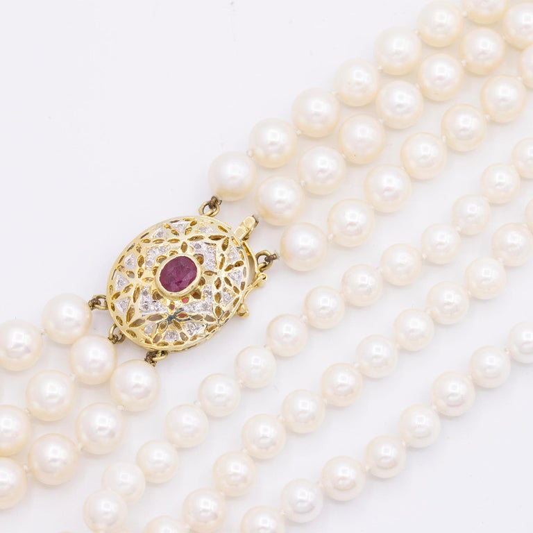 Vintage 14kt Yellow Gold 3 Strand Cultured Akoya Pearl Necklace. It has one oval shaped Ruby & Diamonds on the clasp. It has 168 Cultured Akoya pearls. This necklace is 16