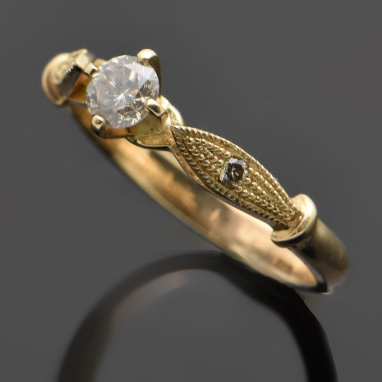 A 14kt yellow gold ring featuring a diamond estimated at 0.30ct. The shoulders are raised into a leaf-like design with beautiful milgran details and diamond accents.   Estimated weight of gold is 2 gr.   We will size it for you.