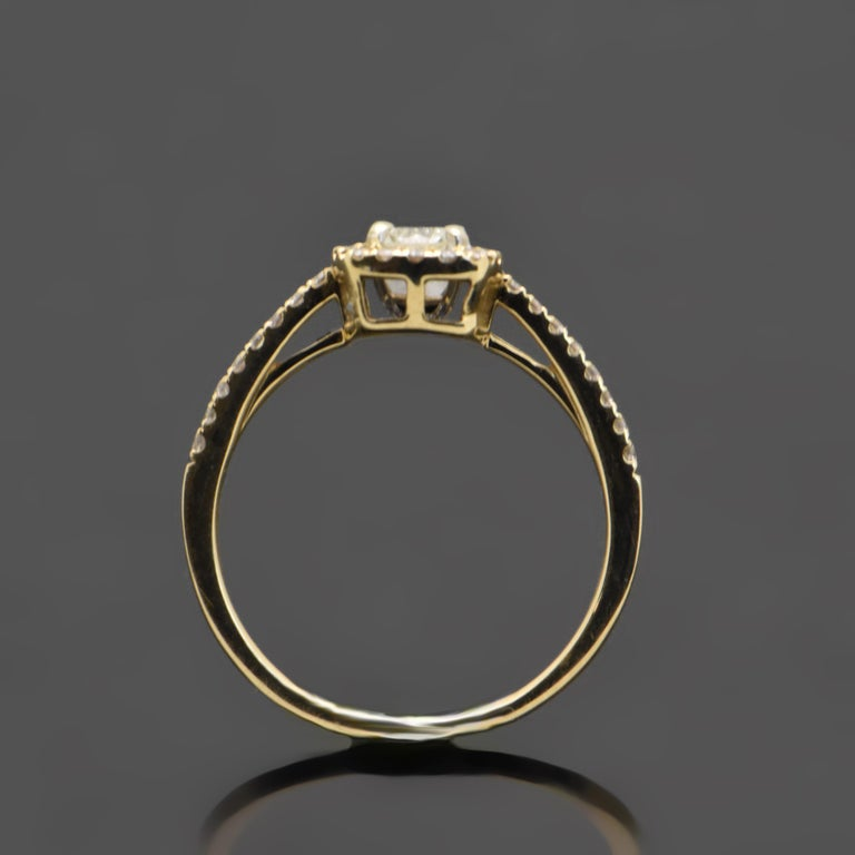This 14kt yellow gold ring features a center cushion-cut diamond with an estimated weight of 0.32ct surrounded by a diamond halo and diamonds down the shank with an estimated 0.21cttw. Estimated weight of gold is 1 gr.   We will size it for you.