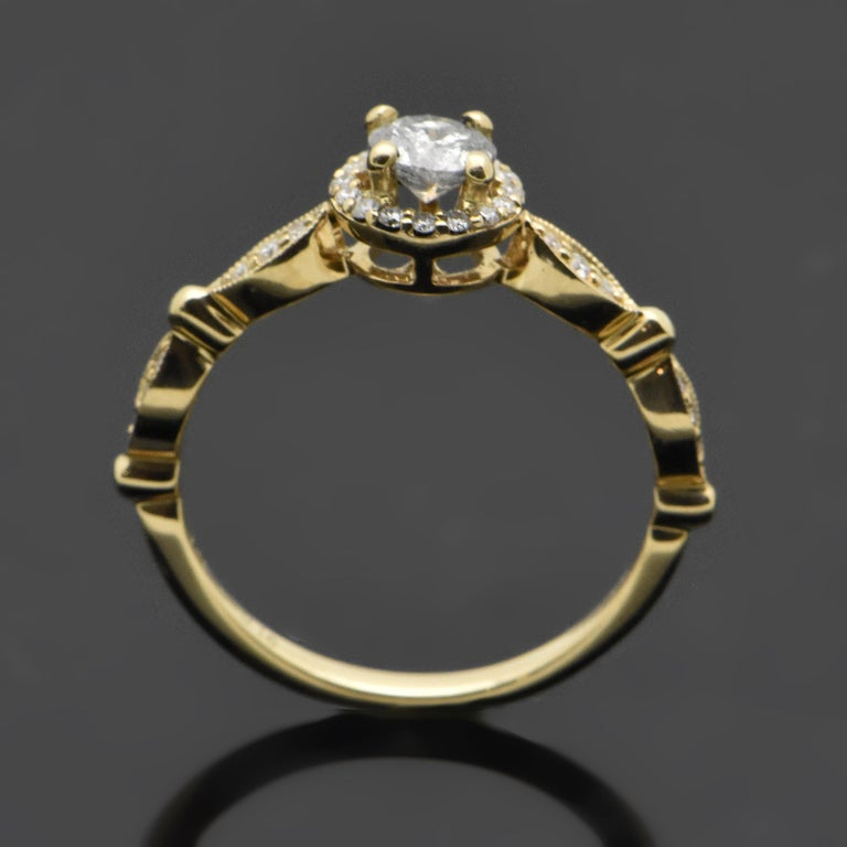 This delicate ring is 14kt yellow gold set with a center diamond estimated at 0.38ct with a 4 prong setting and milgrain details. The halo and side diamonds are estimated 0.16cttw. Estimated weight of gold is 2 gr.   We will size it for you.