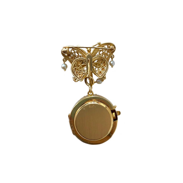 The 14 karat yellow gold brooch has a detachable hand painted miniature. The butterfly contains 14 pearls and may be worn alone. The movement has been converted to Swiss quartz for convenience.