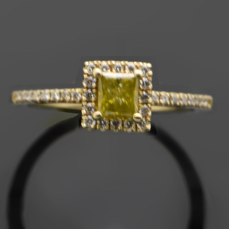 This 14kt yellow gold ring features a princess-cut, yellow diamond with an estimated weight of 0.40ct. Additional diamonds form a square halo and accents down each shank. These diamonds are an estimated 0.18cttw. Estimated weight of gold is 2 gr.
