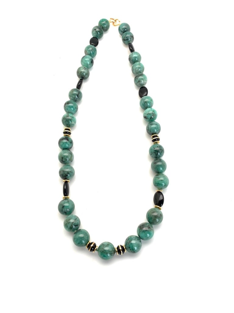 So unusual! Large (14mm) emerald beads are featured in this beautiful necklace. The emeralds are a rich, varigated, emerald-green color, mottled with black. Their color resembles jade. While the beads are opaque, they are emeralds, just the same,
