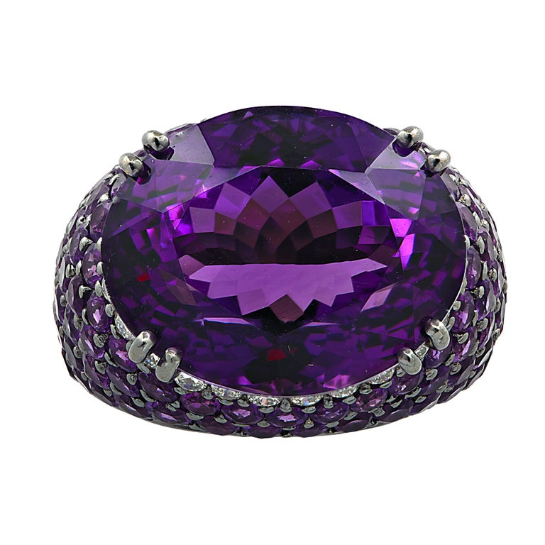 Magnificent cocktail ring crafted in 18 karat white gold and black rhodium, showcasing a sensational oval amethyst weighing approximately 15 carats adorned with 24 round brilliant cut diamonds weighing approximately 0.5 carats total, G color, VS
