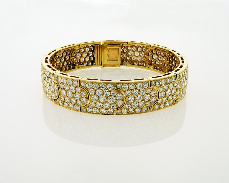 Designed as a pavé-set circular-cut diamond band with interlocking motifs. Total of 345 diamonds adding to approximately 15.00 carats, set in 18K yellow gold. The diamonds are G-H color, and VS clarity. 2 1/4 ins. diameter.   Signed Cartier, no.