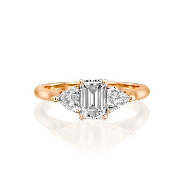 Stunning three-stone style GIA certified diamond engagement ring. Ring features a 1 carat emerald cut natural diamond of F-G color and VS2-SI1 clarity and it is accompanied by 2 smaller trapezoid/trillion shaped diamonds of approx: 0.5 total carat