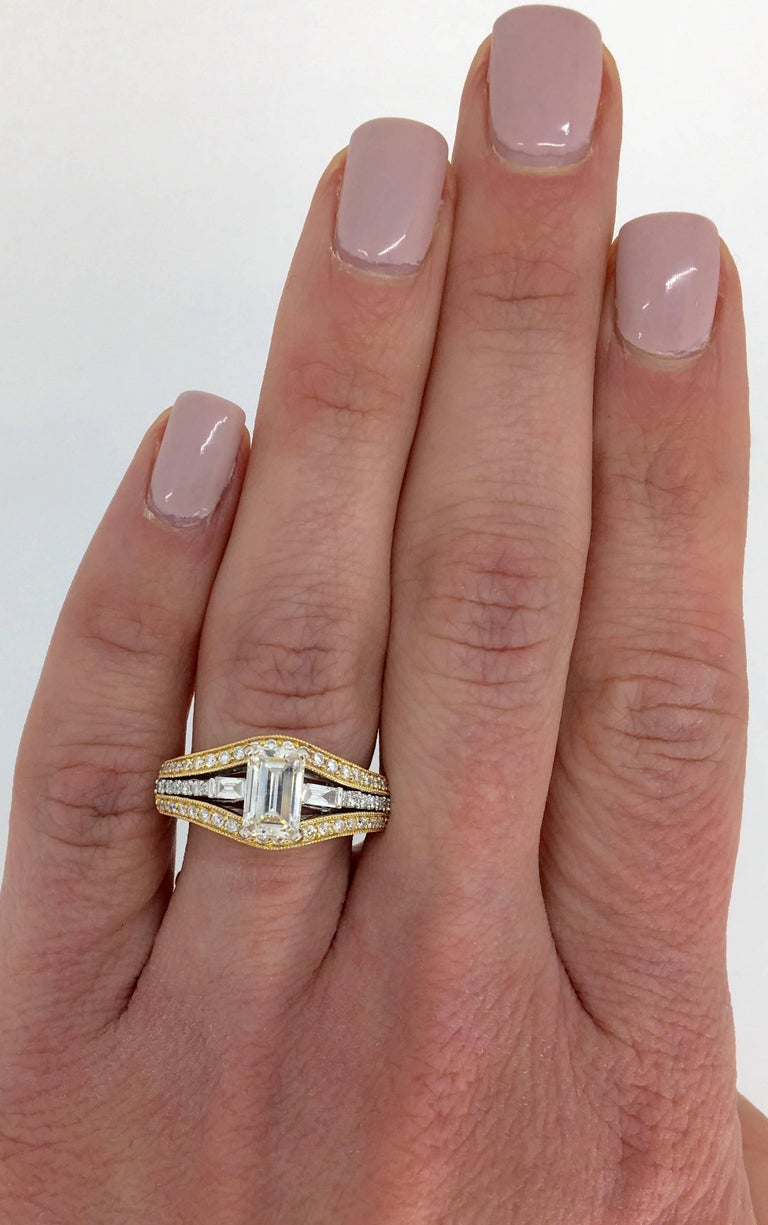 Unique two-tone diamond engagement ring with a 1.00ct Emerald cut diamond in the center, and 0.50ctw of Baguette and Round Brilliant cut diamonds surrounding it.   Center Diamond Carat Weight: 1.00CT Center Diamond Cut: Emerald Cut  Center Diamond