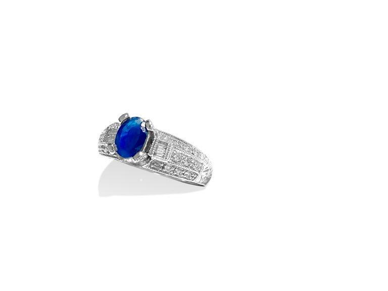 Metal: 18k white gold  Blue Sapphire: 1.50 carat center. Oval shape set in prongs. 100% natural earth mined. Cornblue color and deep saturation   Diamonds: 1.00 carats total. VS-SI clarity and G-H color.  Round brilliant and baguette cut diamonds.
