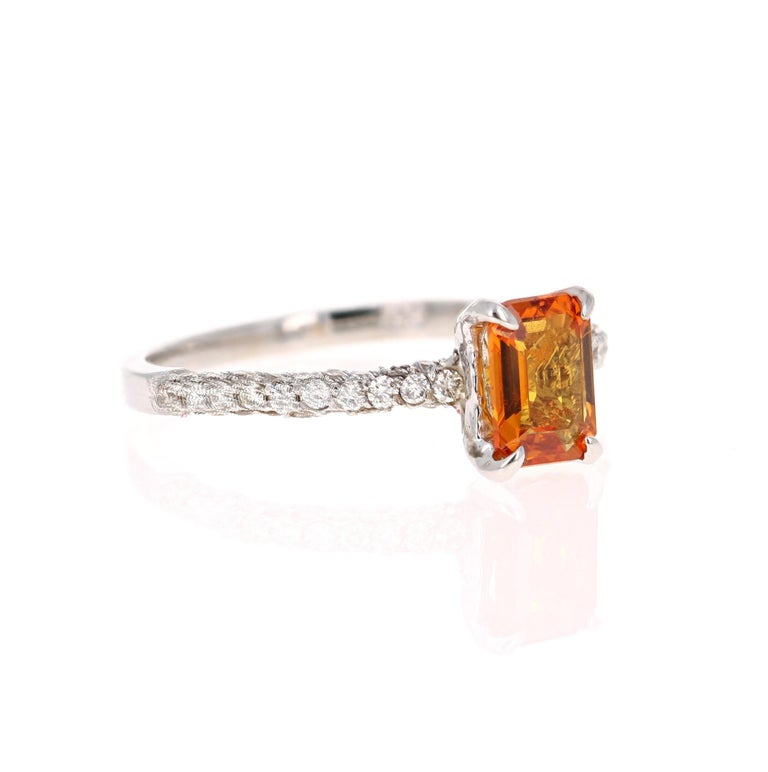 This beautiful ring has Natural Emerald Cut Orange Sapphire that weighs 1.04 Carats and is surrounded 54 Round Cut Diamonds that weigh 0.46 Carats. The total carat weight of the ring is 1.50 Carats.   The ring is beautifully set in a classic 14
