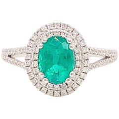 1.50 Carat Oval Emerald and Diamond Halo Engagement Ring White Gold Diamond Band
