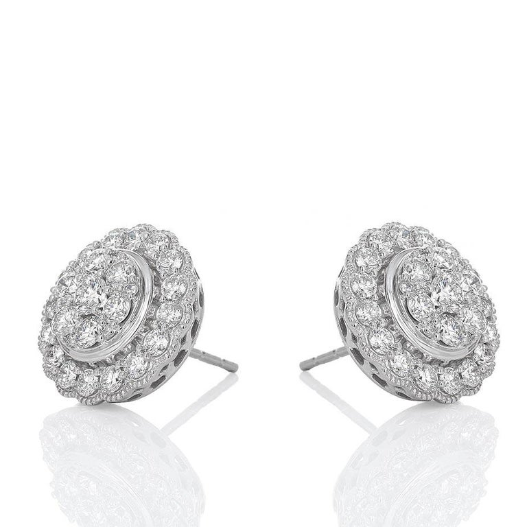 14 karat white gold diamond cluster earrings. There is an estimated 1.50 carats total weight in round brilliant white diamonds, h-i color and vs-si clarity. The center is composed of 1 large diamond with 6 medium sized diamonds surrounding it. There