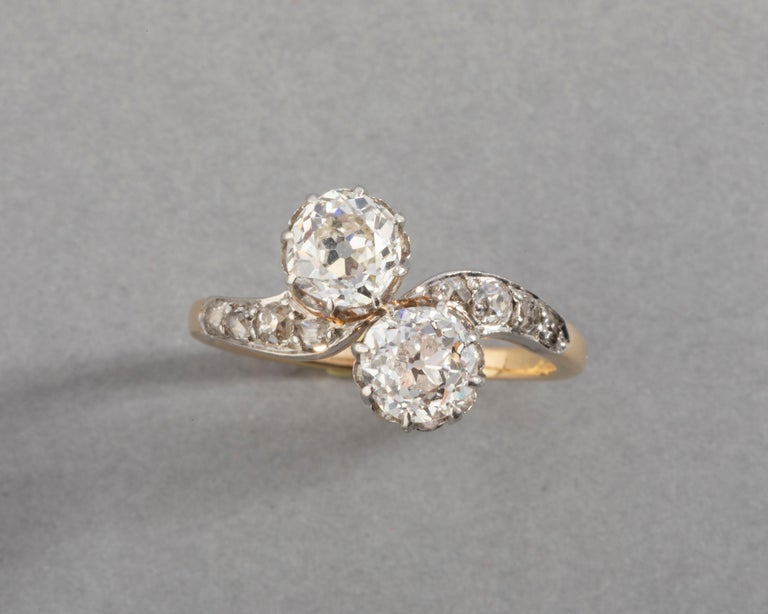 1.50 Carats Diamonds French Antique Toi et Moi Ring  Very beautiful antique ring. Craft in gold 18k (eagle head mark) and platinum. The two principal diamonds are round cut, old european cut. They weight 0.70 and 0.80 carats each estimate. The