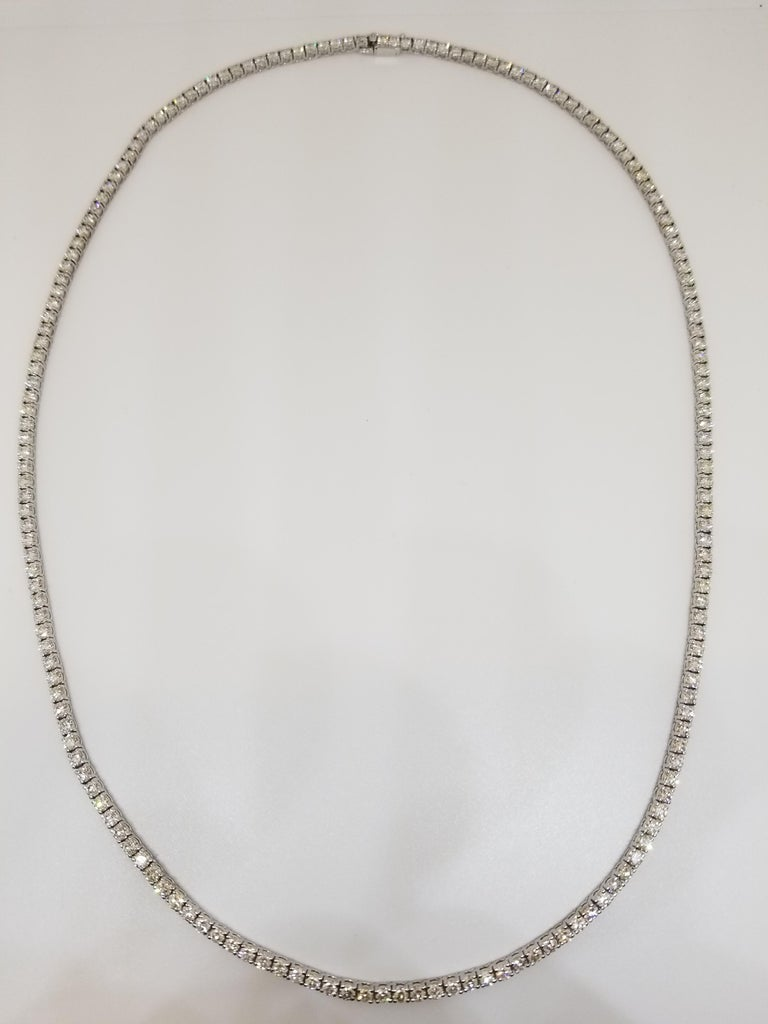 Stunning 14 Karat White Gold Round Brilliant Cut Diamond Tennis Necklace set on 4 prong setting. The total diamond weight is 15 carats. The closure is an insert clasp with safety clasp. Length is 22 inches. I color vs clarity.