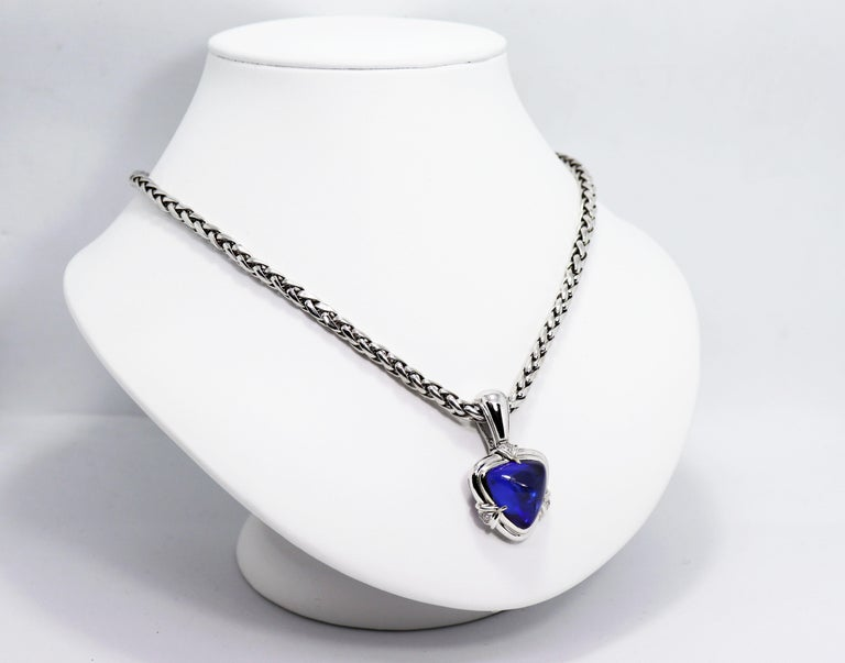 Beautiful necklace featuring a trillion shaped rare AAA+ grade vivid blue cabochon tanzanite weighing an impressive 15.05 carat in a rub-over, open back setting. The mount is further pavé set with nine brilliant cut diamonds weighing approximately