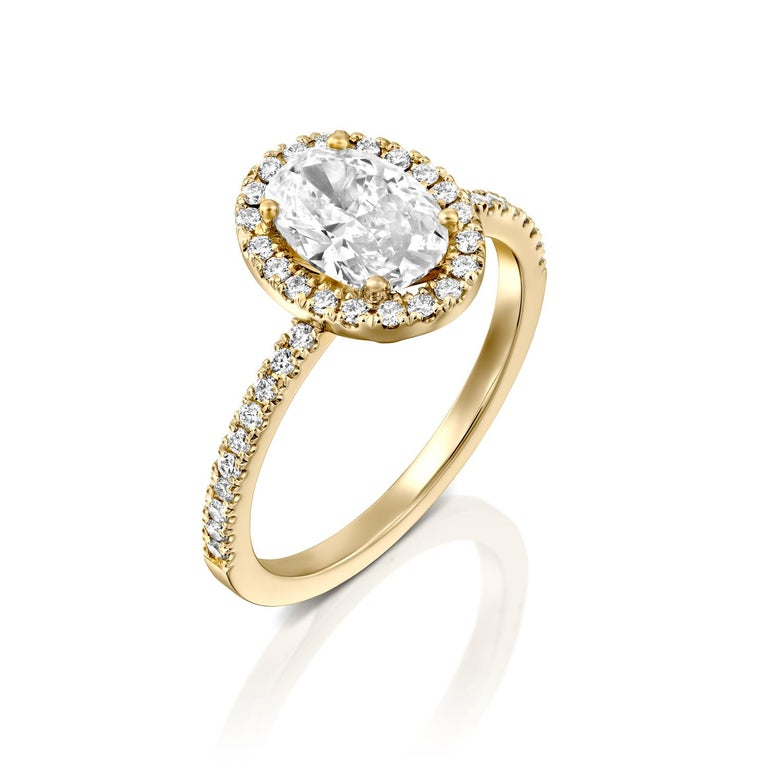 This impressive ring features a solitaire GIA certified oval diamond. Center stone is 1 carat oval cut 100% eye clean natural diamond of F-G color and VS2-SI1 clarity and it is surrounded by smaller natural round diamonds of 0.5 total carat weight.