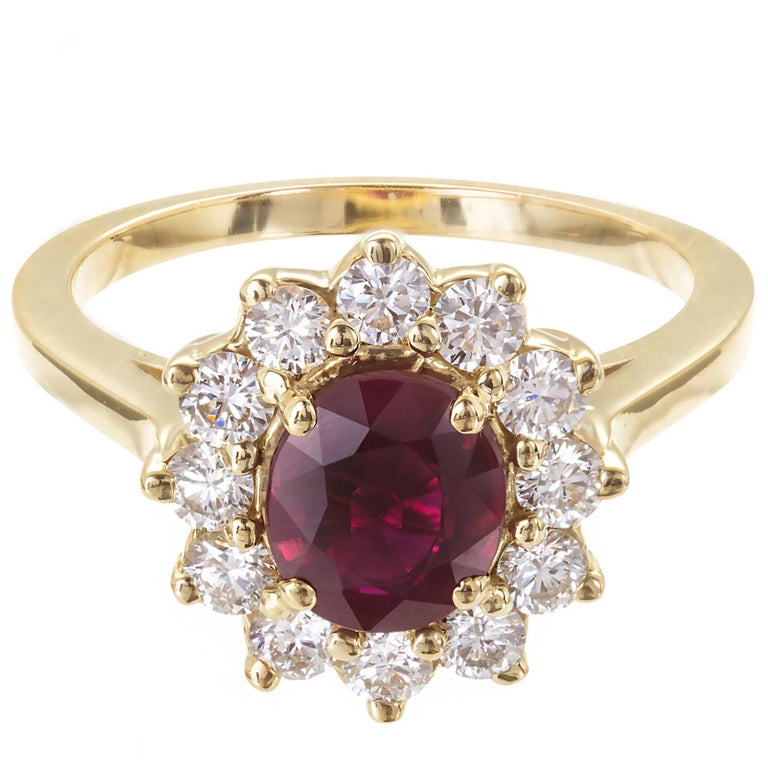 Ruby and diamond halo engagement ring. Excellent brightness and saturation. Heat with minor residue. Simple oval cluster with fine white sparkly diamonds in 18k yellow gold setting.  1 oval Red Ruby, approx. total weight 1.51cts, VS, 7.12 x 6.12 x
