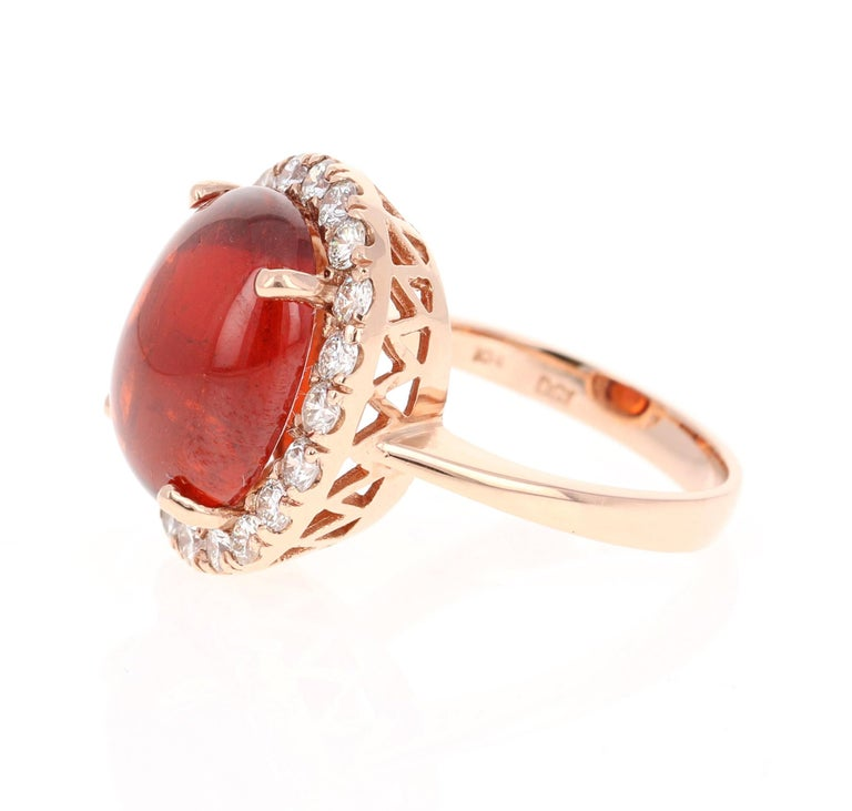 This breath taking ring has a 14.05 Carat Oval Cabochon Cut Spessartine Garnet. Spessartines are natural gemstones found in the Garnet family. It has 20 Round Cut Diamonds that weigh 1.09 Carats. The clarity and color of the diamonds are VS2-H. The