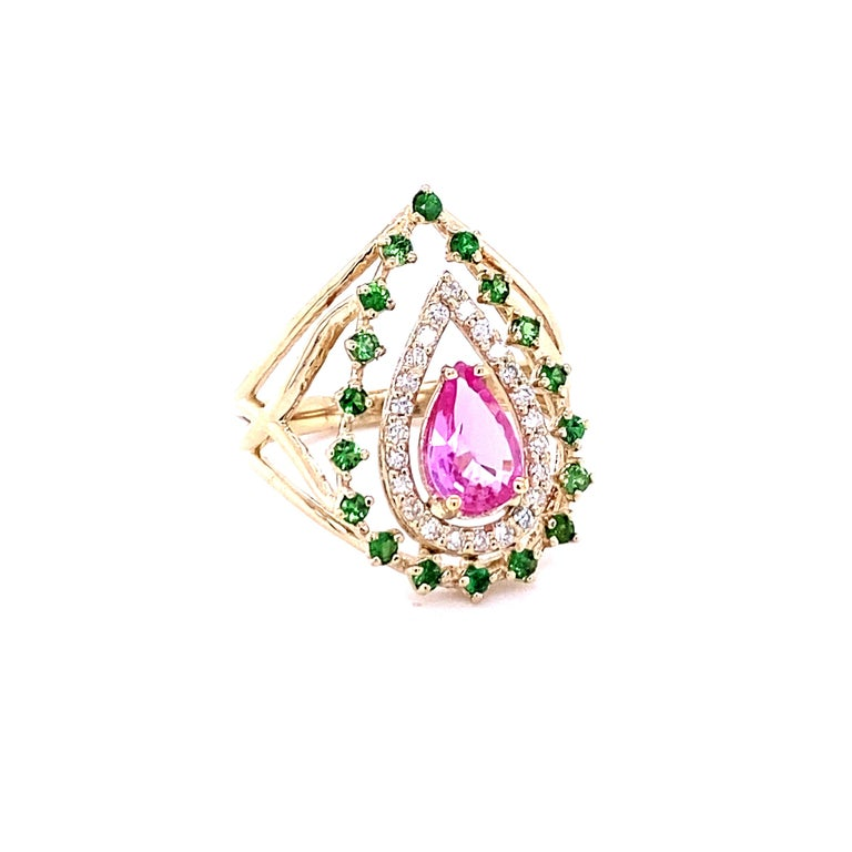 This beautiful ring has a Pear Cut Pink Sapphire that weighs 0.93 Carats. The ring is embellished with 24 Round Cut Diamonds that weigh 0.23 Carats (Clarity: VS, Color: H) as well as 19 Tsavorites that weigh 0.36 Carats.  The total carat weight of