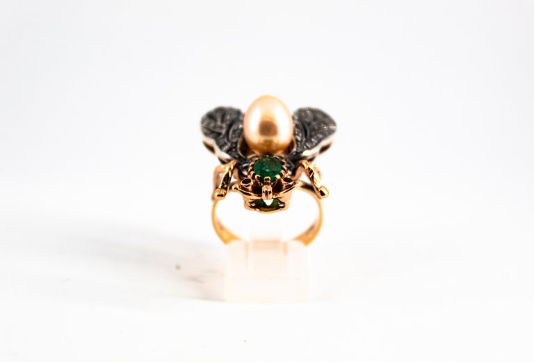 This Ring is made of 9K Yellow Gold and Sterling Silver. This Ring has 0.50 Carats of White Rose Cut Diamonds. This Ring has a 1.00 Carats Emerald. This Ring has 0.04 Carats of Rubies. This Ring has two Pearls. This Ring is inspired by Art