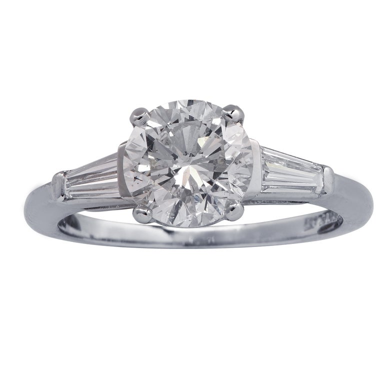 Stunning engagement ring crafted in platinum, showcasing a round brilliant cut diamond weighing 1.53 carats, I color, Si2 clarity, adorned with 2 tapered baguette cut diamonds weighing approximately .30 carats total G color VS clarity. The band