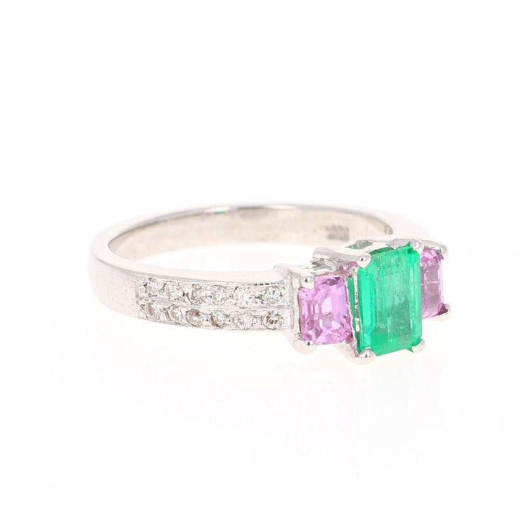 Beautiful and Unique Emerald, Pink Sapphire, and Diamond Three Stone Ring. A beautiful alternative to the classic diamond three stone ring.   This ring has an Emerald Cut Green Emerald that weighs 0.65 Carats with 2 Emerald Cut Pink Sapphires on