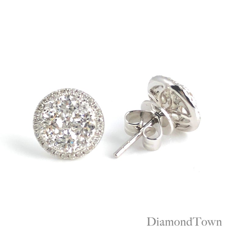 These stud earrings feature a cluster of round white diamonds, surrounded by an additional halo of round white diamonds. Set in 18k White Gold.  Many of our items have matching companion pieces. Please inquire.  An insurance appraisal certificate