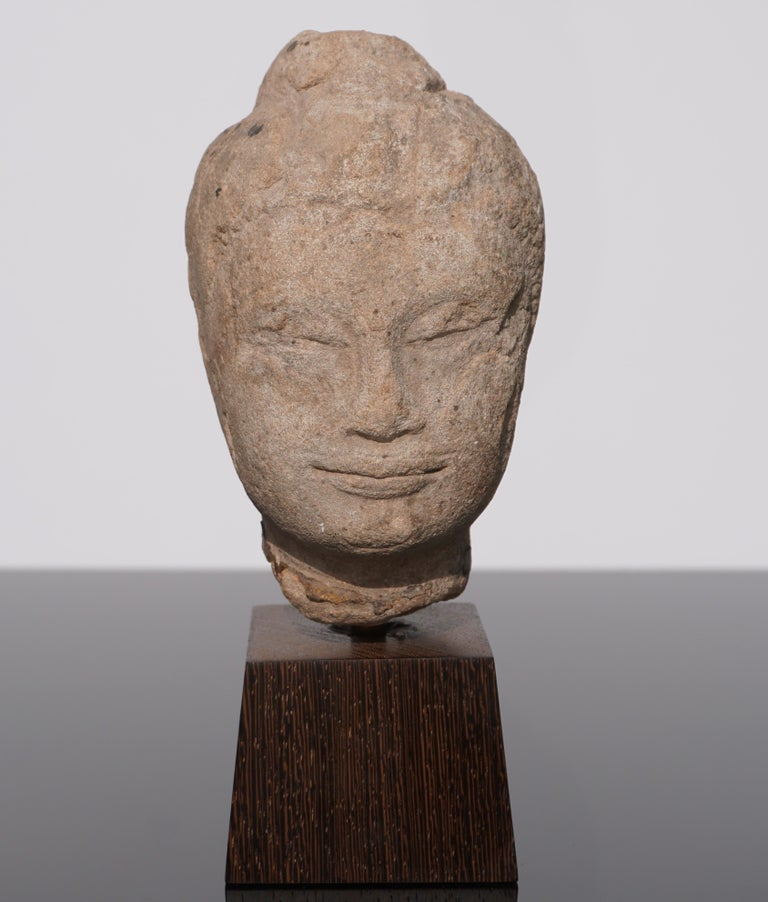 A very serene and calming weathered sandstone Buddha head from Thailand circa 16th century or earlier. Traces of thick gold gilding on neck. I love the feeling this Buddha sculpture figure evokes!  Head: 6 x 4 x 3.75 inches With Stand: 8.25