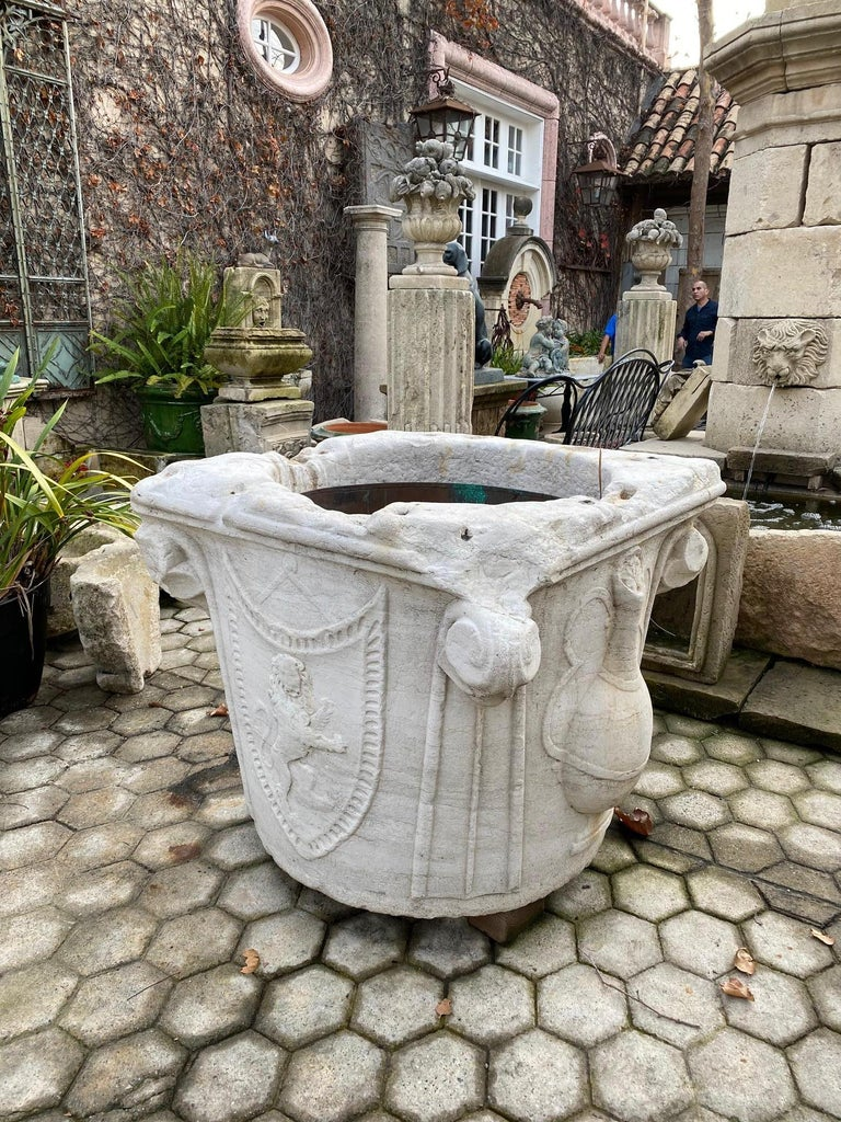 A rare and impressive Historic Italian 15th century Renaissance hand carved marble well head square shape with scrolls to the corners. Decorated with 3-dimensional vessels and armorial with a rampant lion with raised forelegs as if to strike and