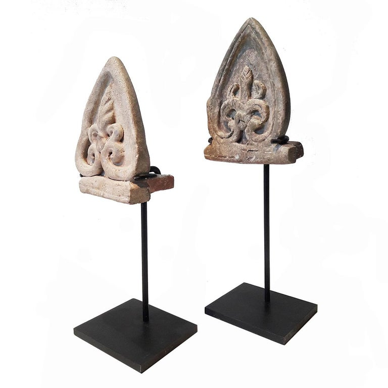Two small ceramic shields from the old kilns of Sukhotai, Thailand, circa 15th century. Used traditionally as architectural details. Mounted on black metal stands. Sold separately. Dimensions of the tallest one (on stand) are specified below.