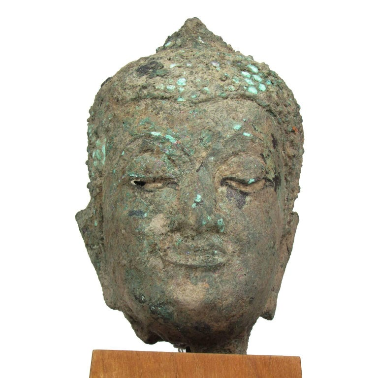 15th century bronze head of Buddha, Thailand, Ayutthaya. Heavy patina (formerly buried), missing finial. Measures: Height of head 9 inches. Exceptional provenance from the collection of the late Sarah M. Bekker.