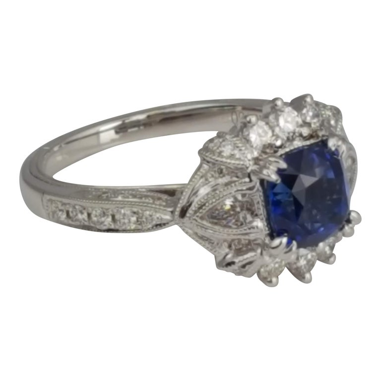 (DiamondTown) This gorgeous ring holds a 1.60 carat cushion cut blue sapphire center, set among 0.63 carats pear shape and round diamonds. Hand engraved milgrain work and old world design elements bring a classic elegance to this piece.  Center: