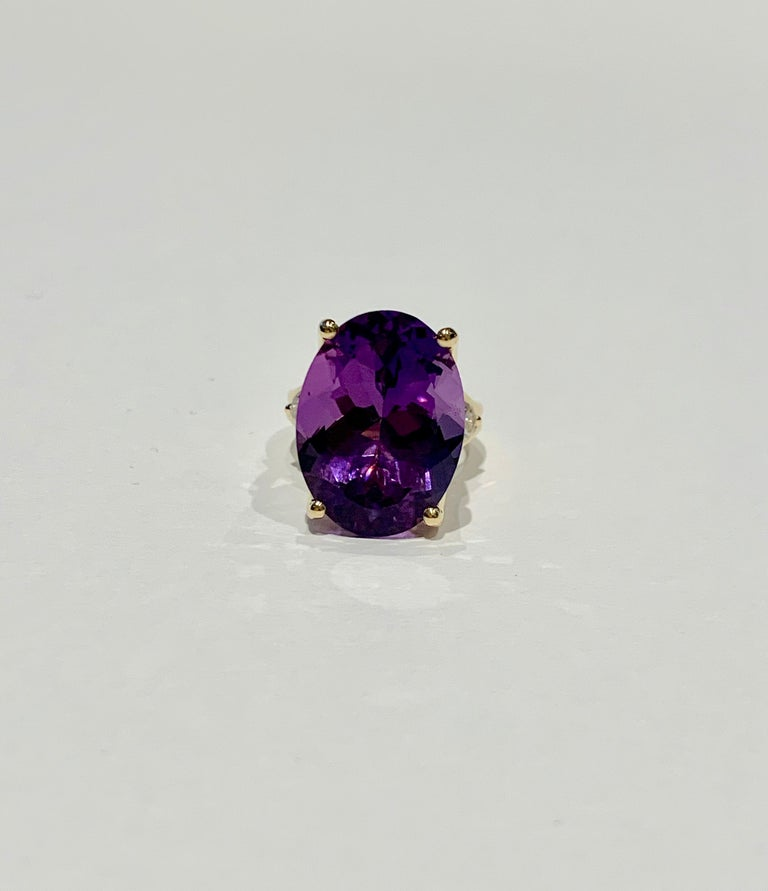This BESPOKE cocktail ring features a beautiful 16 ct dark purple oval Amethyst* which is the Birthstone for February.  The Amethyst has wonderful transparency and is set in a double band of 18ct Yellow Gold with four claws and two .25ct round