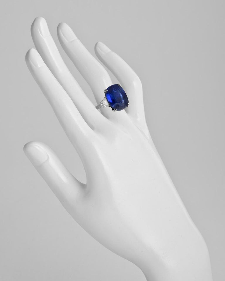 Ceylon sapphire and diamond ring, centering a natural no-heat cushion-shaped sapphire weighing 16.04 carats, flanked by a trapeze-cut diamond at either shoulder, the pair of diamonds weighing approximately 1.06 total carats, mounted in platinum.
