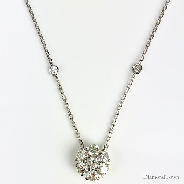 This lovely pendant features seven round diamonds arranged in a flower shape (diamond weight 1.33 carats). Eight additional diamonds placed along the chain bring the total diamond weight to 1.61 carats.  Chain measures 17