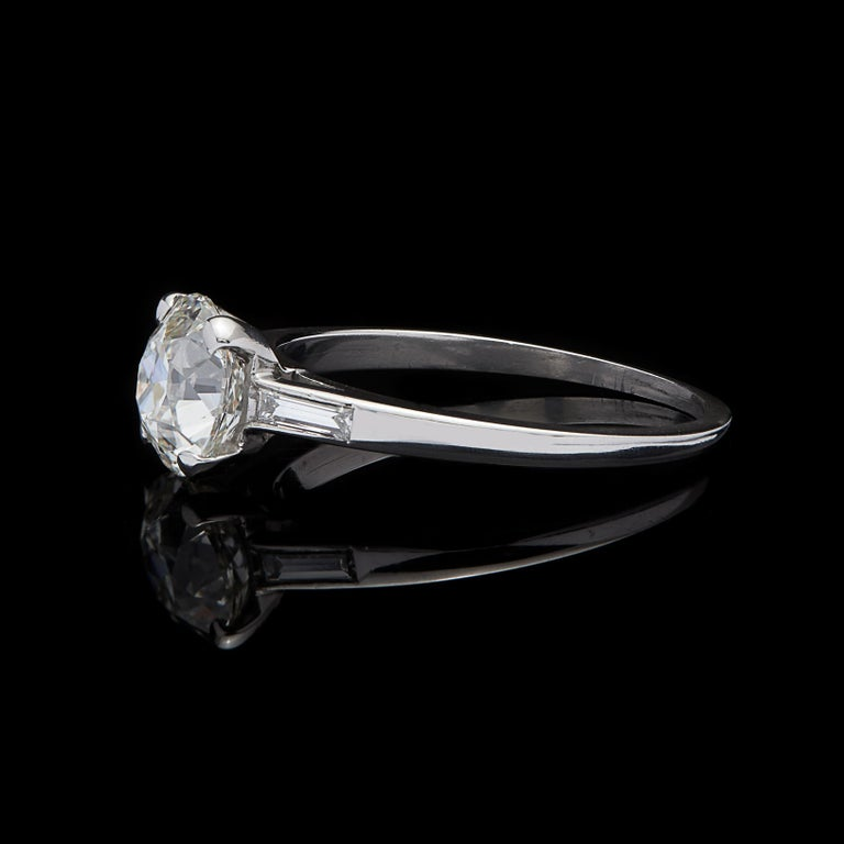 With old world charm and beauty, this 1930's platinum engagement ring features a 1.63-carats Old European-cut diamond (graded K/SI), flanked on either side with a straight baguette-cut diamond. Total diamond weight for the ring is an estimated 1.75
