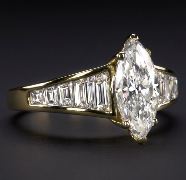 1.68 carat carat marquise cut diamond in a sleek and sophisticated diamond encrusted setting. The certified diamond is bright white and completely eye clean. Measuring an eye catching 12.17mm across, the marquise cut has excellent coverage and a