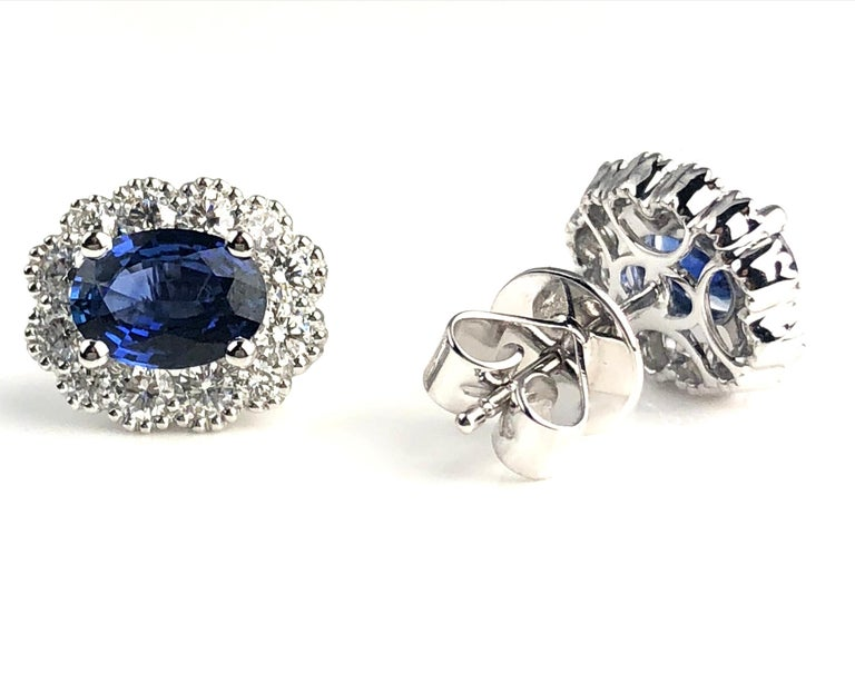 These lovely earrings feature an oval cut vivid blue sapphire (total weight 1.67 carats), surrounded by a a halo of round white diamonds (total weight 0.78 carats).  Many of our items have matching companion pieces. Please view our other listings or