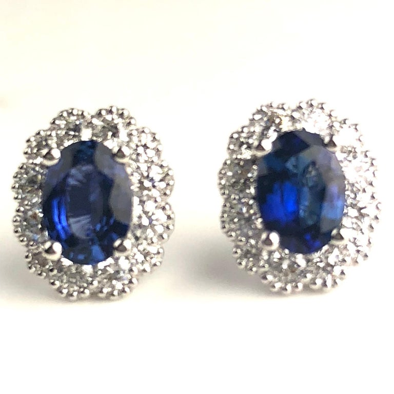 Contemporary 1.67 Carat Oval Cut Blue Sapphire Earrings with Diamond Halo in 18k White Gold For Sale